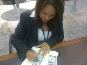 U.S. Treasurer Rosa Rios signs notes for collectors at the U.S. Mint display